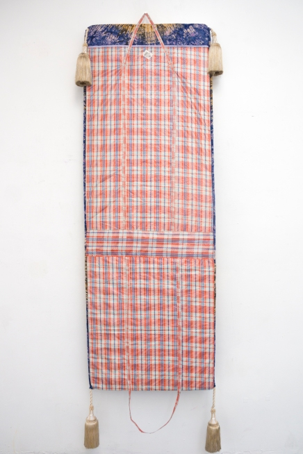 "Must Go [When I Getto London],2018. High-density foam, Ghana-Must-Go bag, Nigerian tie-dye fabric, rope, tassels.27"" x 3"" x 80"""